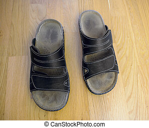 two used house shoes on a parquet floor