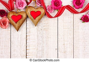 Two Valentines Day wood hearts with paper roses against white wood