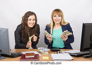 Two very happy office girl happily holding wads of money in their hands and look in the frame