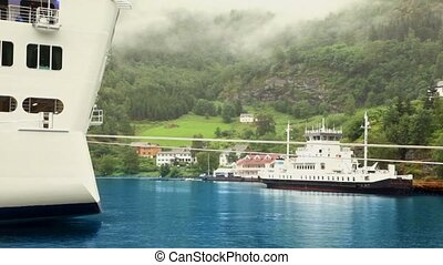 Two vessels on moorage near coastal town under mountain with...