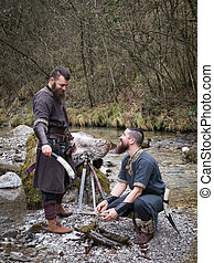 two Vikings in the forest on the banks of the river