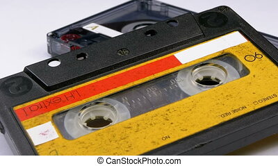 Two Vintage Audio Cassette Rotates on White Background. Transparent and yellow Retro tape cassette with a blank label. Old music. Close-up.
