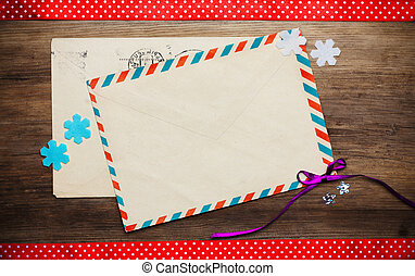 two vintage envelopes on wooden background with ribbons