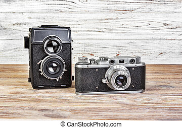 two vintage photo camera on a wooden background