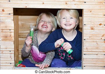 Two vivacious beautiful little blond twin girls
