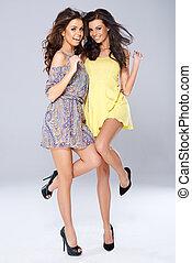 Two vivacious beautiful young women in trendy short summer...