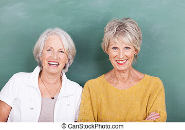 Two vivacious attractive elderly ladies standing side by side laughing at the camera against a green blackboard