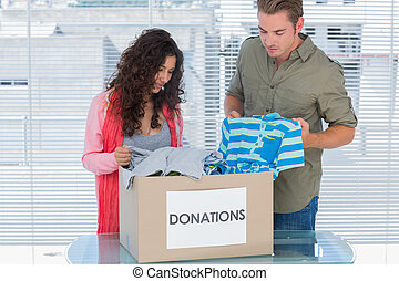 Two volunteers taking out clothes from a donation box for a ...
