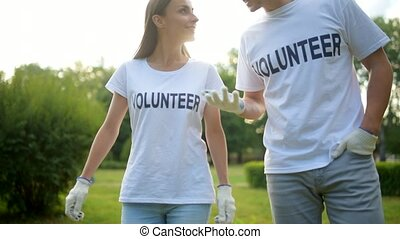 Two volunteers walking around and having chat - Modern role...