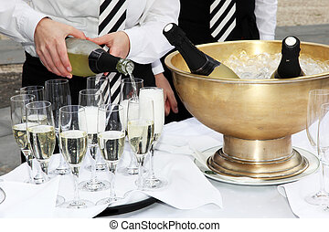 Two waiters fill glasses of champagne at a party.