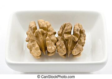 Two Walnuts Kernels in a White Dish