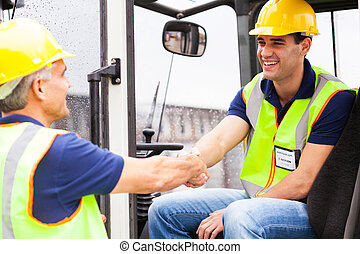 warehouse forklift drivers handshaking - two warehouse...
