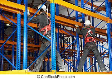 two warehouse workers installing rack arrangement - team of ...