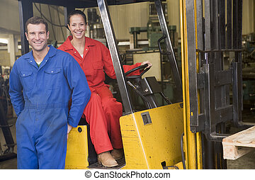 Two warehouse workers with forklift