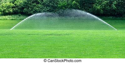 Two water sprinklers on lawn