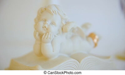 two wedding gold rings. angel figure statuette. angel on book. closeup