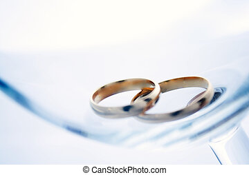 Two wedding rings in a glass