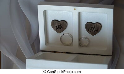 Two wedding rings in a white box with hearts.