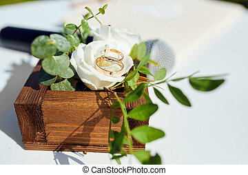 two wedding rings lie on the flowers of roses in a wooden box