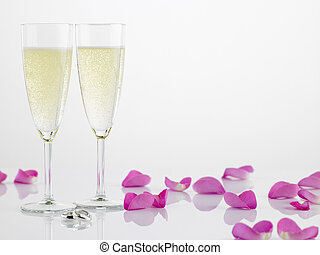 Two Wedding Rings Next To Champagne Flutes And Rose Petals