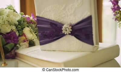 two wedding rings on a cushion tied with ribbon and other...