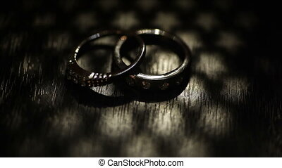 Two wedding rings on a kraft box. Dark scene.