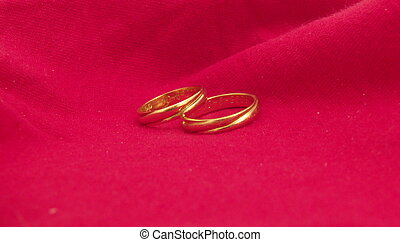 Wedding Rings On A Red Cloth Against The Background Of A Flower