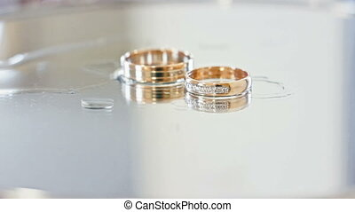 Two wedding rings on mirror table, drops of water, macro