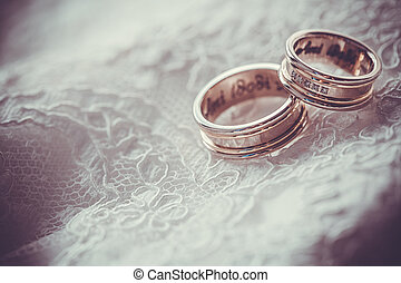 Two wedding rings with brown background