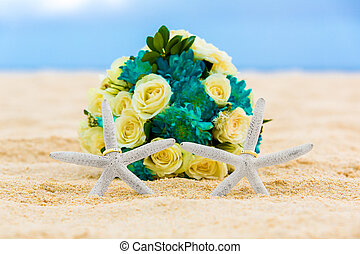 Two wedding rings with two starfish and wedding bouquet on a...