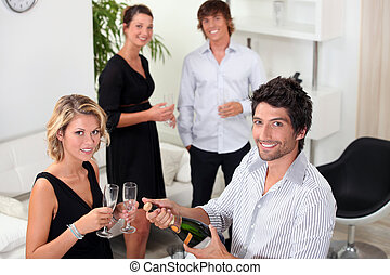 two well dressed couples drinking sparkling wine in a living...