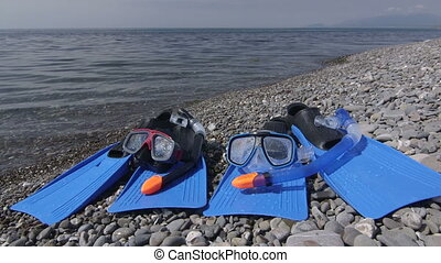 Two wet snorkeling sets fins scuba masks on wild pebble...