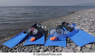Two wet snorkeling sets fins scuba masks on wild pebble beach in summer