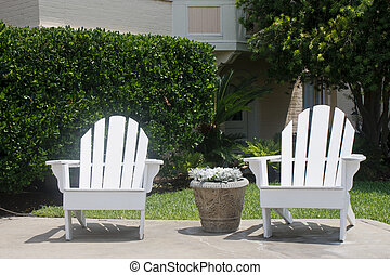 Two White Adirondack Chairs on Patio.