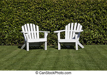 Two white adirondack chairs - White adirondack chairs on a...