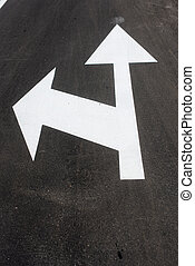 Two white arrows on asphalt