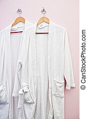 Two white bathrobes hanging on the wall
