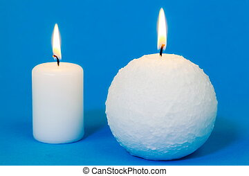 Two white burning candles on blue