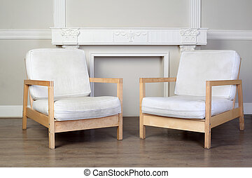 two white chairs and beautiful ornate decorative plaster moldings on wall