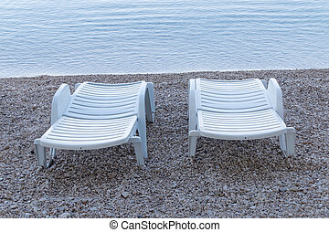 Two white empty deck chair