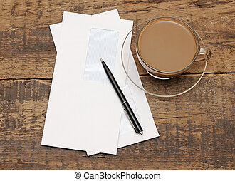 two white envelopes with black pen on wood background