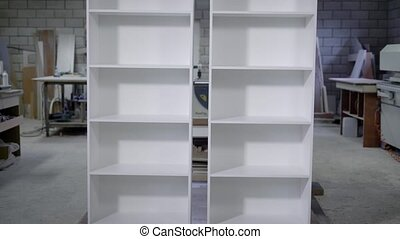 two white finished cupboard with shelves are standing in a...