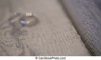 two white golden rings on photo shoot on wooden table outdoors