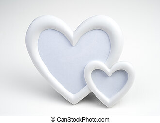 Two white hearts in a close-up frame on a light background.
