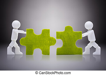 White Human Figures Joining The Green Jigsaw Pieces