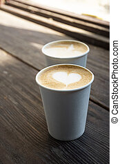 Two white paper cups of coffee on wooden table.