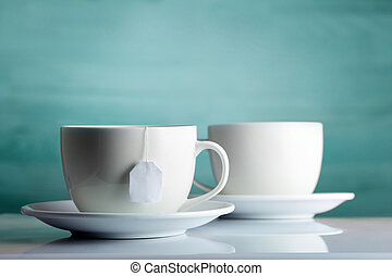 Two white porcelain teacups on white table show clean and...