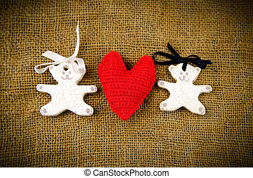 Two white toy bears with red handmade heart on the sacking background