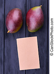 Two whole mangoes and blank paper card. Fresh tropical...