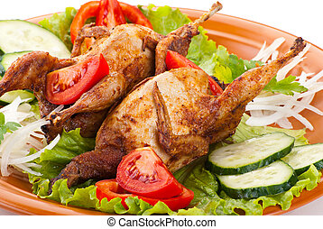 Two fresh grilled whole quail with cucumber, raw tomatoes and onion on plate with leaf lettuce isolated over white background